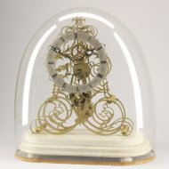 Antique english skeleton clock on white marble basement and under glass dome.