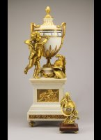 Monumentaal french table circles tournants table clock with a putto and military attributes, the 2 ears of the vase are designed from 2 serpents. 8-day movement signed: G. Chartier, horloger, Paris.