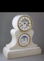 White marble mantel clock with visible 'Brocot'-escapement. Below is an everlasting calendar with moon-, month-, day- date- and equation-indication. The calendar automatically jumps from 28, 29, 30 or 31 to 1, depending the length of the month (February 28>1, leap-years 29>1). De central hand shows the month and the equation correction.